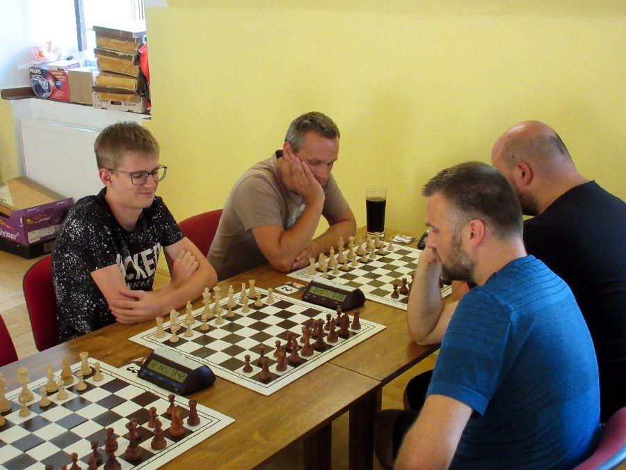 Vlevo v černém tričku za 2. šachovnicí Jan Horák, po jeho levici šachový velmistr Štěpán Žilka.